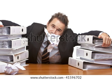 Young businessman is sitting on desk and having paper sheet in his mouth, because of unmanageable work. Isolated on white. - stock photo
