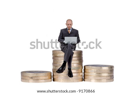Young businessman is sitting with a notebook on some coins. Full isolated studio picture - stock photo