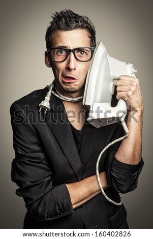 Young businessman is using a flat iron like a phone. - stock photo