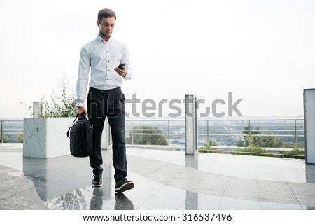 Young businessman is walking with his case. He is writing a message on his mobile phone. Skyline on a background - stock photo