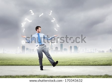 Young businessman juggling with numerals against city background - stock photo