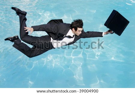 Young businessman jumping into the water in a suit - stock photo