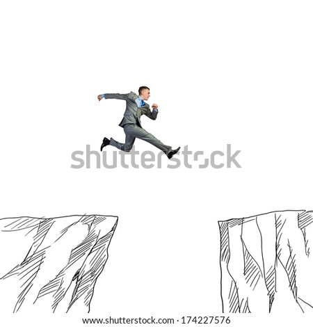 Young businessman jumping over drawn mountain gap - stock photo