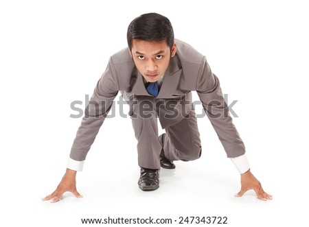 young businessman kneeling as if about to start a race, isolated on white background