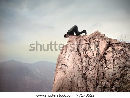 Young businessman kneeling on a mountain peak and looking downwards - stock photo