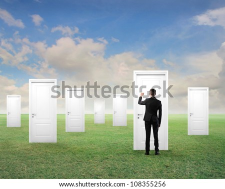 Young businessman knocking at one of many white doors on a green meadow - stock photo