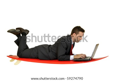 Young businessman laying in a surf board with laptop - stock photo