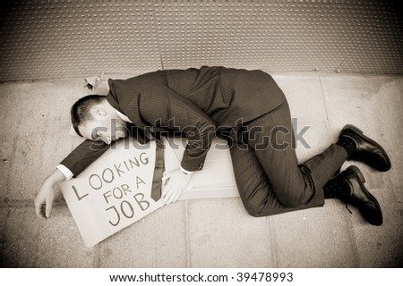 Young businessman laying over a sign Looking for a job - stock photo