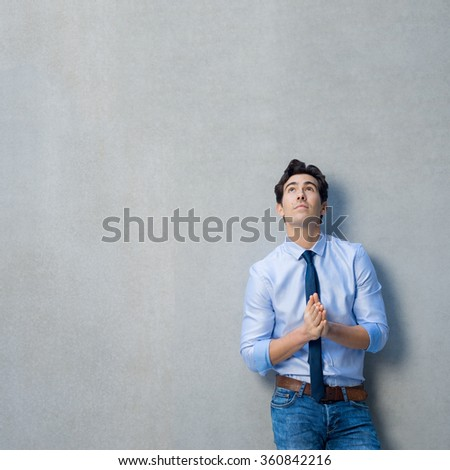 Young businessman leaning against grey wall with palms joint. Pensive man looking up and thinking with copy space. Thoughtful businessman thinking of a new idea or strategy in a grey background.  - stock photo