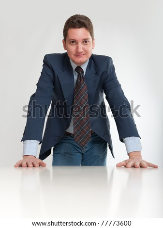 Young businessman leaning on a white desk - stock photo