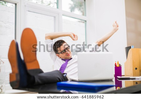 Young businessman lies on a chair, keeps legs on a table and straightened at the office
