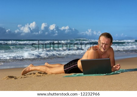 Young businessman lies with notebook on sea beach. Shot in Sodwana Bay nature reserve, KwaZulu-Natal province, Southern Mozambique area, South Africa.