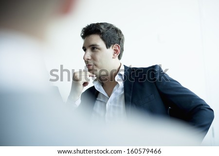 Young businessman listening in business meeting - stock photo