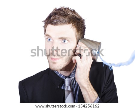 Young businessman listening to a conversation from a telephone can on white background - stock photo