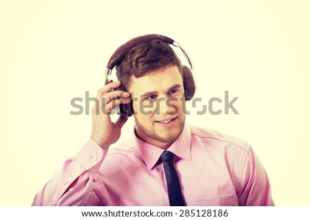 Young businessman listening to music wearing headphones.