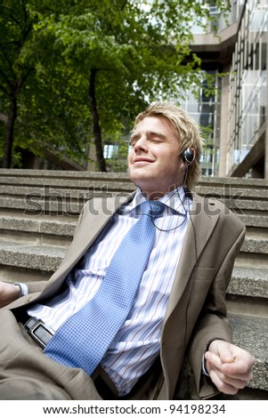 Young businessman listening to music with headphones while sitting down on some steps in the city.
