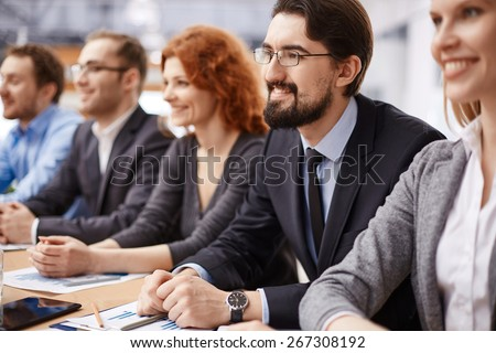 Young businessman listening to speaker among co-workers at conference - stock photo