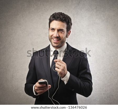 young businessman listens music with earphones - stock photo