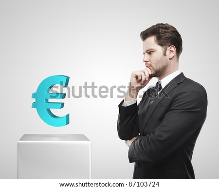 Young  businessman look at the blue Euro sign on a white pedestal. On a gray background - stock photo