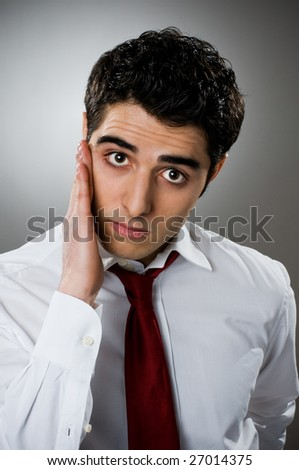 Young businessman looking at camera in a worried and questioning expression