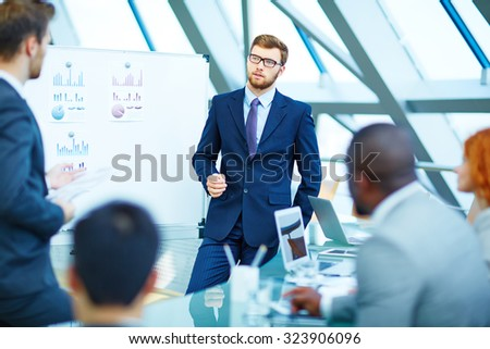 Young businessman looking at colleague while listening to his explanation - stock photo