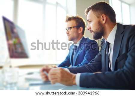 Young businessman looking at computer monitor with colleague near by