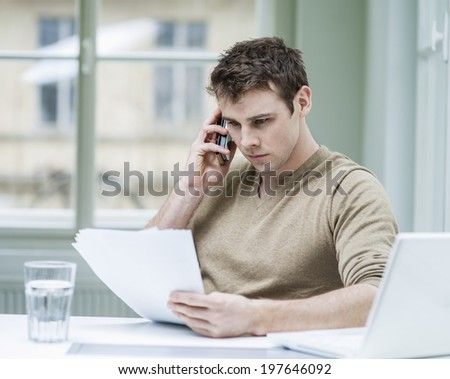 Young businessman looking at documents while using mobile phone in office - stock photo