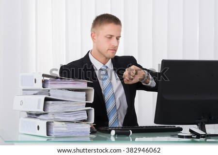 Young Businessman Looking At His Watch In Office