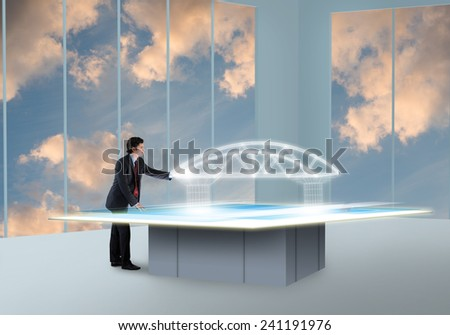 Young businessman looking at hologram of construction project - stock photo