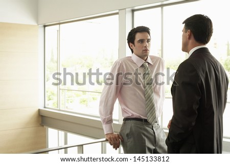 Young businessman looking at male colleague while standing by railing in office - stock photo