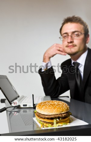 Young businessman looking at sandwich