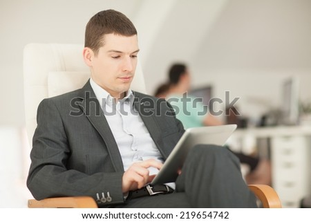 Young businessman looking at tablet computer. - stock photo