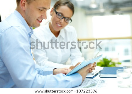 Young businessman looking at touchpad with his secretary near by - stock photo