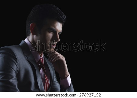 Young businessman looking away against black background