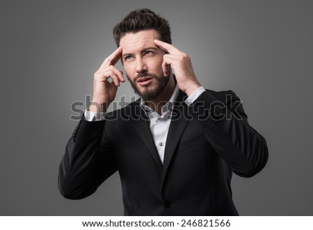 Young businessman looking away and touching temples, brainpower concept - stock photo