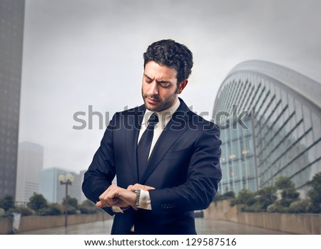 young businessman looking his watch - stock photo
