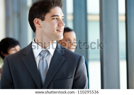 young businessman looking outside office window - stock photo