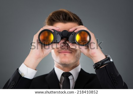 Young businessman looking through binoculars against gray background - stock photo
