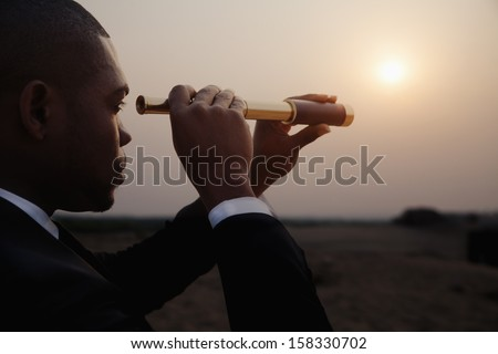Young businessman looking through telescope in the the desert - stock photo