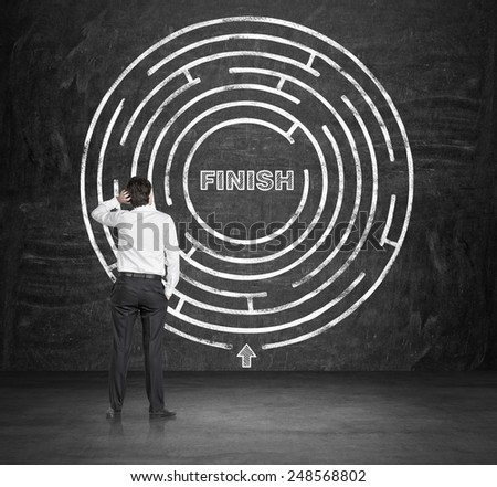 young businessman looking to out way of the maze - stock photo