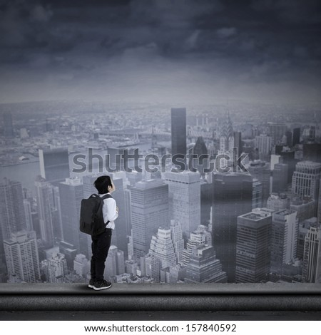Young businessman looking to the future while standing on the top of skyscraper - stock photo