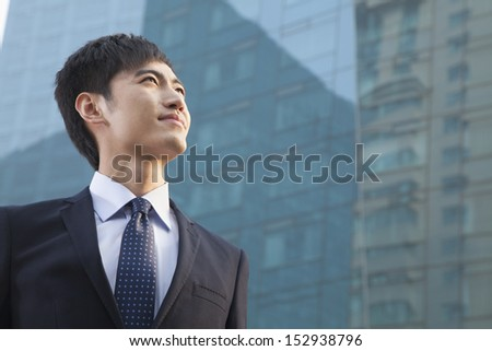 Young Businessman Looking Up, Glass Building, Portrait - stock photo