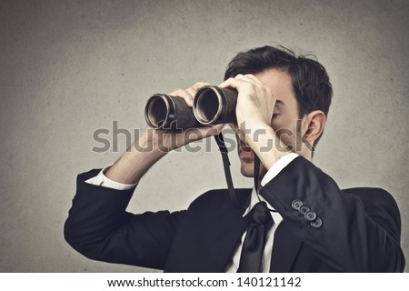 young businessman looking with binoculars - stock photo