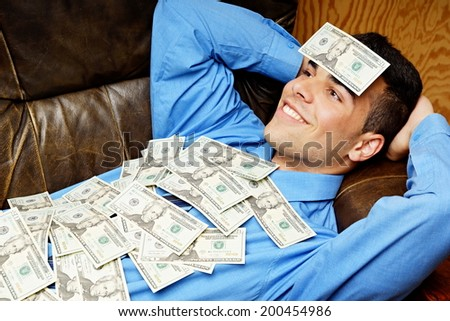 Young businessman lying on the couch and relaxes with money - stock photo