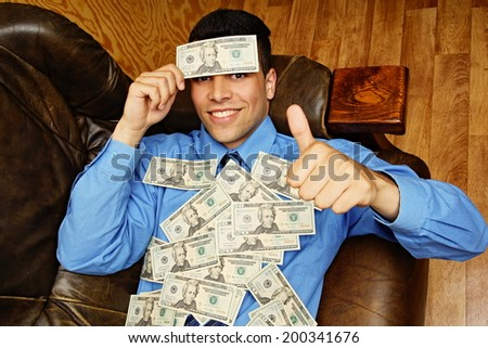 Young businessman lying on the couch with dollar bill on his headed, showing thumb up  - stock photo