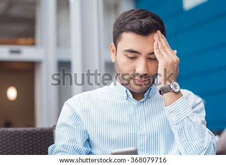 Young businessman made a mistake, something is wrong. Close up of worried man sitting in a bar - stock photo
