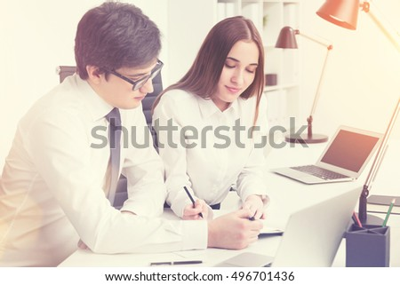 Young businessman making notes together with businesswoman who is sitting next to him. Sunny day. Concept of explanation.  Toned image