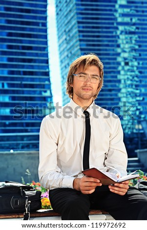 Young businessman making plans in his diary over big city background. - stock photo