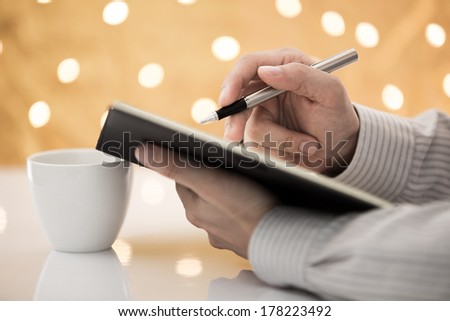 Young businessman making some notes in notebook. - stock photo