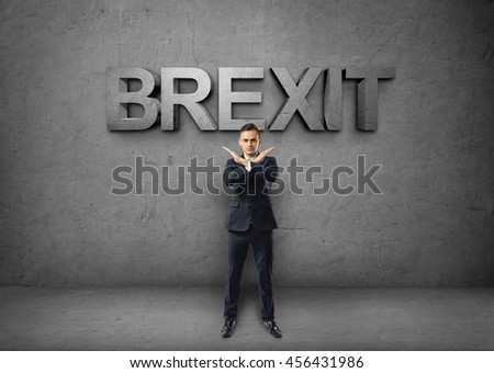 Young businessman making X sign with his arms on the concrete backround with 'brexit' word. Prohibitions and restrictions. Body language. Office clothes. British withdrawal. - stock photo